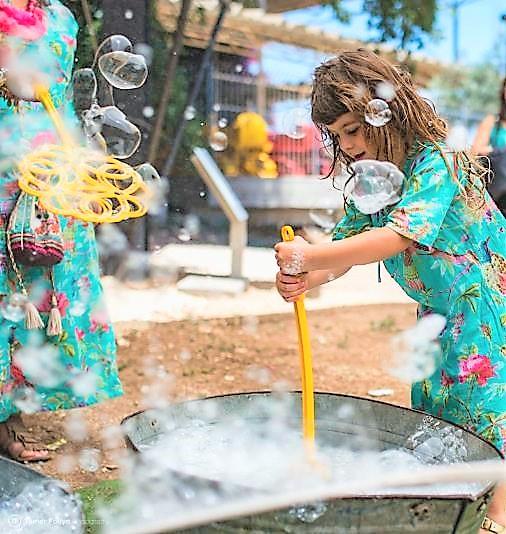ילדה משחקת בבועות סבון